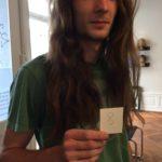 Ein Haarspender am Haarspendetag mit Nummer in der Hand