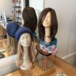 Echthaarperücke und Kopfbedeckung vor Spiegel