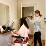 Coiffeuse schneidet einer Frau die Haare ab, die dann für eine Perücke verwendet werden.